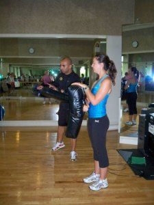 Instructor Marion and Jessica demonstrate kicking exercises for the rest of the class