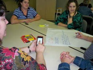 A 2nd grade teacher consults an iPhone to check state standards to include at poetry station practice